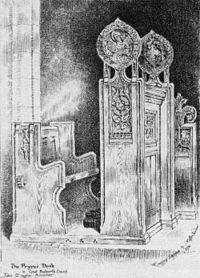 A black and white image showing a church seat on the left and the carved side of the prayer desk in front of it