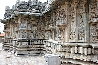 "Nageshvara-Chennakeshava Temple complex, Mosale - Outer wall decoration of the Nageshvara and Chennakeshava temples is of the ""old style""; eaves below superstructure, decorative miniature towers below eaves, wall images below the miniature towers, and five mouldings at the base"