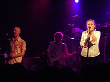 Linda Hopper singing with R.E.M.; singer Michael Stipe and bassist Mike Mills are visible to her left.