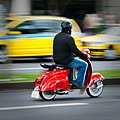 Red scooter rider Avenida Do Mar, Funchal, Madeira Island.jpg