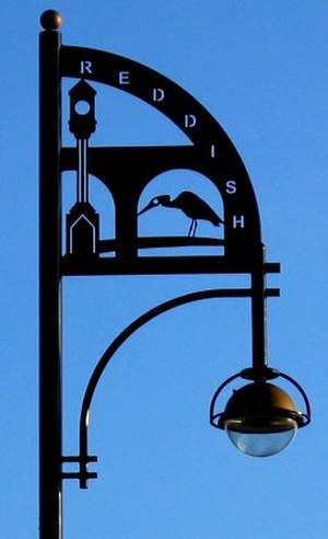 Reddish - A lamp standard near Houldsworth square. It pictures the herons commonly seen in Reddish Vale, the railway viaduct, and the clock monument to Sir William Houldsworth