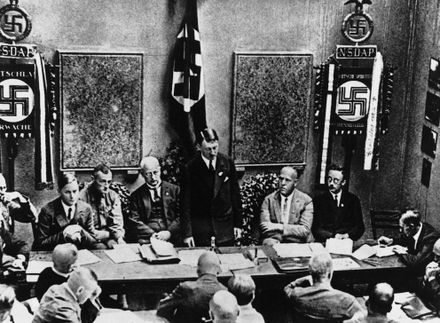 Adolf Hitler (standing) delivers a speech in February 1925 Refoundation.jpg