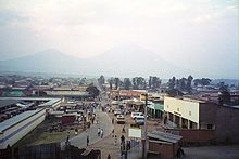 Photograph of Ruhengeri, Rwanda, with buildings, a street, and people visible, and mountains in the background, partially in cloud