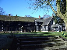 A two-storey black and white timbered building in an L-shape. A wide set of stone steps in the foreground leads onto a grassed area in front of the house.