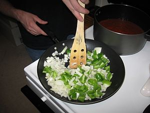 A cook sautees onions and peppers.