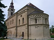 Schoengrabern church, Austria, shows a semi-circular chancel, flat buttresses and arcade beneath the roof. The tower is of the Baroque period.