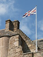 Flag on pole atop a historic building showing the Scottish variant of the Union Flag