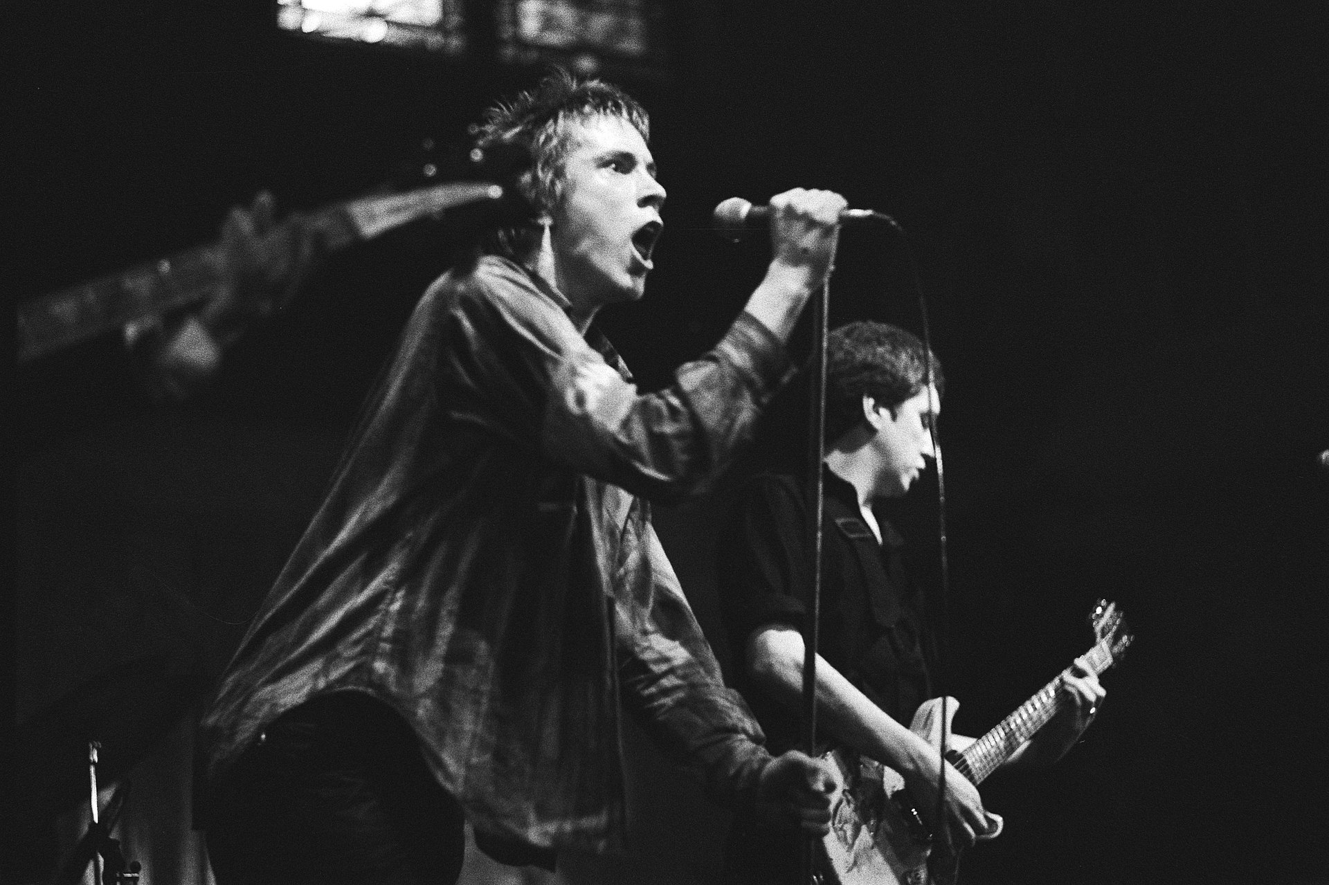 Members of rock band The Sex Pistols onstage in a concert. From left to right, singer Johnny Rotten and electric guitarist Steve Jones.