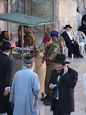 Jewish prayer - An Israeli soldier lays tefillin at the Western Wall (Kotel) prior to prayer.