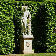 statue on a plinth in front of a green hedge. A youth in classical dress leans against a tree trunk