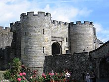 Front of a stone castle gatehouse with round towers in the corners, battlements and an arched entrance.