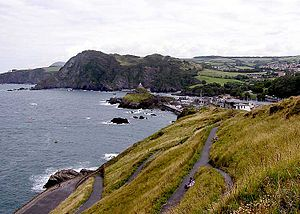 South West Coast Path - The South West Coast Path passes along the cliffs seen in the distance) at Ilfracombe, North Devon. The highest point in this view is Hillsborough (447 feet, 136 metres). Part of Ilfracombe is seen on the right.