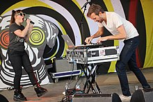 Male and female electronic duo performing together.