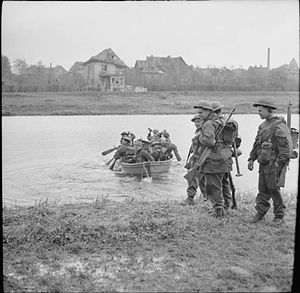 157th (Highland Light Infantry) Brigade - Men of the 7th Battalion, Cameronians (Scottish Rifles) use a small boat to cross a canal in the town of Rheine, Germany, 3 April 1945.
