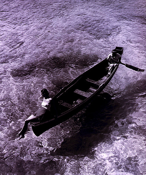 Fashion model on edge of boat, man rowing, Montego Bay, Jamaica. Published in Harper's Bazaar, November 1946. From Visiting Jamaica? 7 Things You Need to Know