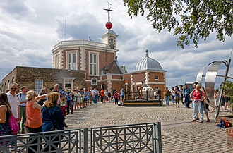 A group of people waiting in a line curving to the left on a cobblestone surface. Behind it is an ornate brick building with a red ball on top. The people at the end of the line, closest to the camera, are taking pictures of other people near a shiny metal monument on the right, under a tree. A line in the cobblestone connects them