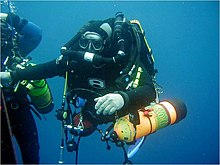 A scuba diver in a wetsuit holds onto the shotline at a decompression stop. He is breathing from a rebreather and carrying a side-slung 80 cubic foot aluminium bailout cylinder on each side. A second diver is partly visible to the left.