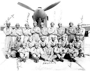 Alabama World War II Army Airfields - Official US Army Air Force Training Command photograph of 20 Tuskegee Airmen posing in front of a P-40; Tuskegee Army Airfield.