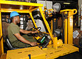 U.S. Marine Corps Lance Cpl. Alex Aikens uses a forklift to pick up humanitarian assistance and disaster relief supplies bound for Pakistan in the well deck of amphibious assault ship USS Peleliu (LHA 5) 100829-N-AB355-007.jpg