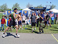 U.S. Navy Petty Officer 3rd Class Anthony Sandoval calls out the finish time for a runner at the Navy SEAL Fitness Challenge in Dearborn, Mich., May 10, 2008 080510-N-TG958-006.jpg