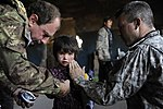 U.S. and Italian medical personnel apply lotion to an Afghan child's face.jpg