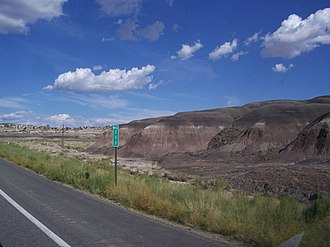 U.S. Route 550 - View of Tertiary sediments of the San Juan Basin Badlands at southbound Mile Marker 111 in New Mexico (36.2558°N 107.6229°W).