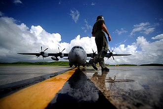 53d Weather Reconnaissance Squadron - A WC-130J Hercules aircraft weather loadmaster of the 53d WRS performs pre-engine start-up inspection in St. Croix, Virgin Islands, on 16 September 2010. The SFMR antenna housing is visible under the starboard wing outboard of the number four engine.