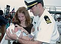 US Navy 030713-N-1159B-007 Lt. Robert Naudin Jr. holds his seven-week-old son for the first time as his wife looks on.jpg