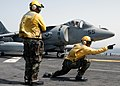 US Navy 040411-N-8053S-072 A plane director and shooter assigned to the amphibious assault ship USS Wasp (LHD 1) signal the AV-8B Harrier pilot that he is clear for launch.jpg