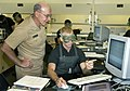 US Navy 040903-N-5390M-004 Chief of Naval Operations (CNO), Adm. Vern Clark, looks on as Midshipmen 4th Class Daniel Walker explains his most recent lab work.jpg