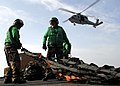 US Navy 060325-N-4166B-032 An MH-60S Seahawk helicopter assigned to the Island Knights of Helicopter Sea Combat Squadron Two Five (HSC-25), passes over two Sailors as they pull a cargo net on into position.jpg