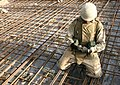 US Navy 060616-N-9712C-009 Steelworker 3rd Class Robert Sprague ties together rebar before a concrete placement on a bridge project.jpg
