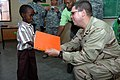 US Navy 071215-N-3931M-101 Capt. Dennis Gallagher from Combined Joint Task Force-Horn of Africa (CJTF-HOA) presents a gift to a local student at a school dedication ceremony in Ali Adde.jpg
