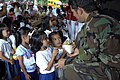 US Navy 071227-N-7286M-033 A U.S. Navy SEAL (Sea Air Land) team member hands out rice and canned foods to students of Panunsulan Elementary School on the island of Basilan during a Medical Civic Action Program (MEDCAP).jpg