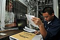 US Navy 080731-N-7981E-032 Personnel Specialist 3rd Class Ferdirick Domingo, from San Diego, Calif., assists a Sailor with his Navy cash card account in the disbursing office aboard the Nimitz-class aircraft carrier USS Abraham.jpg