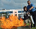 US Navy 081008-N-0311M-156 Richard Niles, a Naval Air Station Key West firefighter, teaches a boy how to properly use a fire extinguisher during an annual Fire Safety Fair at Sigsbee Park, Fla.jpg