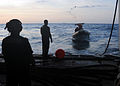 US Navy 091121-N-1291E-026 Members of Helicopter Mine Countermeasures Squadron (HM) 15 in a rigid hull inflatable boat (RHIB) throw a line to Aviation Electronics Technician Airman Anthony Skubon to launch a MK-105 Mod 4 Sled.jpg