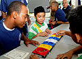 US Navy 100504-N-8377A-065 oatswain's Mate Seaman William Massey plays a board game with students during a community service project at the Sekolah Rendah Sultan Umar Ali Saifuddin School.jpg