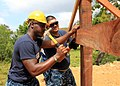 US Navy 110201-N-4630B-039 Ship's Serviceman 3rd Class Corderra Lee and Chief Logistics Specialist Glen Aguilus work together to hammer a pillar as.jpg