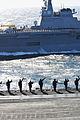 US Navy 110404-N-DM338-398 Sailors and Marines aboard USS Ronald Reagan (CVN 76) wave to Japanese sailors aboard JDS Hyuga (DDH 181) during a pass.jpg