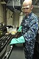 US Navy 110722-N-EE987-008 Personnel Specialist 3rd Class Vasile Mesaros, from Las Vegas, cleans a Mossberg shotgun in the armory aboard the aircra.jpg
