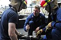 US Navy 110729-N-WV964-106 Damage Controlman 1st Class Kevin Clark instructs Sailors how to apply a banding strip to a pipe during basic damage con.jpg