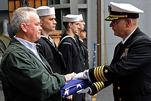 US Navy 111209-N-XE109-085 A Sailor presents the national ensign.jpg