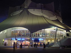 A white illuminated building that resembles a circus tent