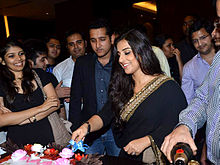 Actress Vidya Balan cuts a cake celebrating the success of Kahaani while actor Parambrata Chatterjee watches, along with several others.