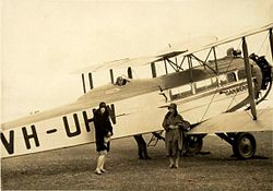 Two women standing in front of large biplane with man in flying gear seated in open cockpit