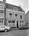 foto van Door rechte lijst afgesloten woninggedeelte, gebouwd boven een doorgang met een natuurstenen poortboog aan de straat