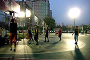 Evening pickup basketball game in a Beijing neighborhood.