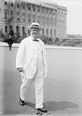 A man in his mid-sixties, wearing a white suit and hat with a black bow tie, walking in front of a building