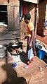 Woman frying cassava slices.jpg